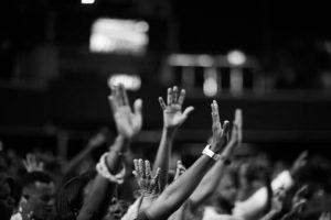 Une foule de personnes lèvent la main
